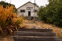 A set of wooden steps leading up to a small abandoned school stock images