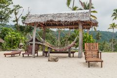 Set of wooden stools and tables for visitors placed under coconut palm trees on the white sands of the beach facing Malet island. Port Olry village in N.E Stock Photo