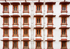 Set of wooden windows on several floors of a building Stock Photos