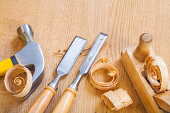Set of woodworking tools chisel hammer plane on wooden board Royalty Free Stock Photography