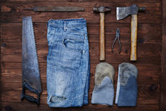The set of working tools, gloves and jeans on a grunge backgroun Stock Photography