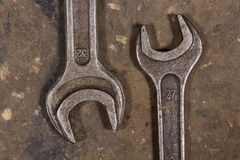 Set of wrenches on oiled floor of the garage. Two wrenches of various sizes lie on the floor, huddled together Stock Images