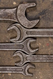 Set of wrenches on oiled floor of the garage. Wrenches of various sizes lie on the floor, huddled together Royalty Free Stock Images