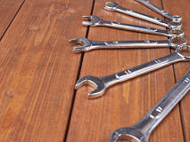 Set of wrenchs chrome metal spanner instruments on wooden surface Stock Photography
