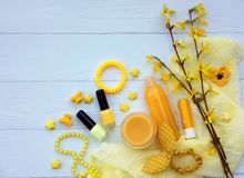 Set of yellow accessories for young girl or teenager. Nail polishes, lipstick, hair clips, bands, beads, bracelet, perfume and fl stock photography