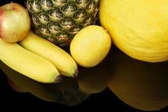 Set of yellow fruits-pineapple,citrus,bananas on black at the bottom Royalty Free Stock Photo
