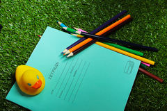 Set for young schoolboy. School bright set of notebooks and colored pencils and rubber ducks Royalty Free Stock Photo