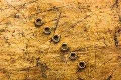 Set złote dokrętki na drewnianym tle Zdjęcie Royalty Free