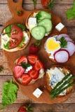 Set zdrowy całej banatki chleb ściska z fuits, warzyw, serowych i obfitolistnych zielonymi ziele na pyknicznym drewnianym stole,  obraz stock