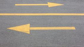 Seta amarela direita e esquerda na estrada do steert do asfalto Foto de Stock
