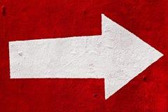 Seta branca no concreto vermelho. Imagens de Stock