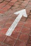Seta branca pintada em um assoalho do estacionamento Imagens de Stock