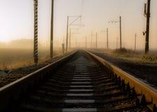 Seta branca pintada nos dorminhocos da estrada de ferro que saem na distância foto de stock