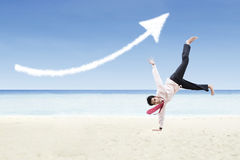 A seta da dança e do aumento do homem de negócios assina a nuvem na praia Fotografia de Stock