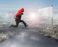 Seta levando de salto do homem de negócios acima do sinal embandeirar no penhasco Imagem de Stock Royalty Free
