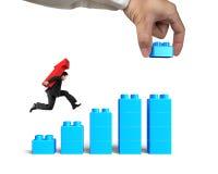Seta levando do homem que corre acima a construção da mão do bloco do gráfico de barra Foto de Stock