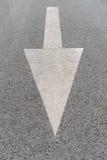 Seta pintada branca na estrada asfaltada cinzenta Imagem de Stock