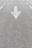 Seta pintada branca na estrada asfaltada cinzenta Fotos de Stock Royalty Free
