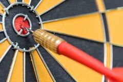 Seta vermelha do dardo do close up que bate no bullseye do alvo do alvo Imagens de Stock Royalty Free
