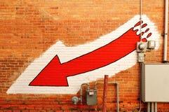 Seta vermelha pintada em uma parede de tijolo foto de stock