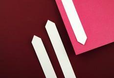 Setas de papel no papel da cor do bordo Imagens de Stock Royalty Free