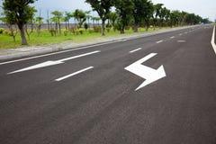Setas dos sinais de estrada na superfície asfaltada Fotografia de Stock Royalty Free