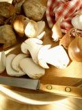 Setas en la tarjeta de corte con los chalotes, las cebollas y el ajo Fotos de archivo libres de regalías