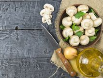 Setas frescas con las hojas perejil y cebolla y aceite en una tabla de madera rústica La comida vegetariana está en la tabla E Imagen de archivo