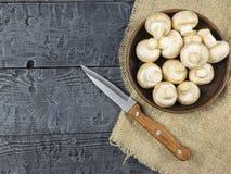 Setas frescas con perejil de las hojas en una tabla de madera rústica La comida vegetariana está en la tabla La visión desde la t Imagen de archivo libre de regalías