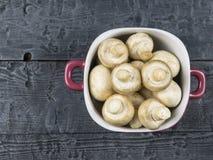 Setas frescas en un cuenco púrpura en una tabla de madera rústica La comida vegetariana está en la tabla La visión desde la tapa Imagenes de archivo