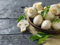 Setas frescas en un cuenco y un perejil de la arcilla en una tabla de madera rústica oscura La comida vegetariana está en la tabl Imagenes de archivo