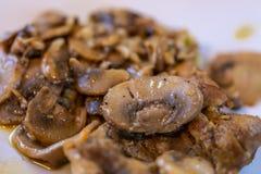 Setas fritas en una placa de cer?mica blanca Descensos del aceite vegetal foto de archivo libre de regalías