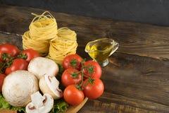 Setas, lechuga, tomates y espaguetis de las setas en la tabla de madera Imagenes de archivo