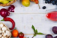 Setas, uva, ciruelos, cebolla, tomates, pimientas de chiles, vidrio de vino rojo, manzanas y peras en cesta Visión desde arriba Imágenes de archivo libres de regalías
