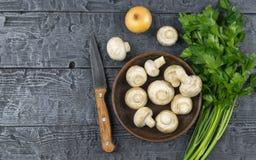 Setas y cebolla y perejil frescos en una tabla de madera rústica La comida vegetariana está en la tabla La visión desde la tapa Imagenes de archivo
