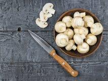 Setas y cuchillo frescos en una tabla de madera rústica La comida vegetariana está en la tabla La visión desde la tapa Fotografía de archivo libre de regalías