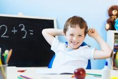 Sete anos felizes do menino idoso na sala de aula Imagem de Stock