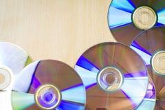 Sete CD na textura de madeira da tabela/fundo fotografia de stock royalty free
