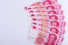 Sete chineses 100 notas de RMB arranjadas como o fã isolado nos vagabundos brancos Fotos de Stock Royalty Free