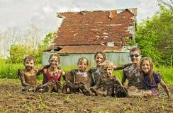 Sete crianças do país sentam-se na poça de lama do jardim junto Fotos de Stock