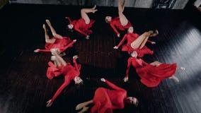 Sete dançarinos fêmeas estão encontrando-se em um assoalho na figura redonda, estão movendo-se e estão levantando-se, vista super video estoque
