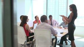 Sete empresários que têm a reunião em torno da tabela da sala de reuniões video estoque