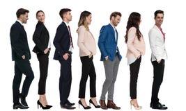 Sete executivos novos modernos que esperam na linha fotografia de stock