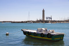 Sete, France. A boat with tires and a buoy with the lighthouse Phare du Mole Saint-Louis in the background. Sete, France stock images