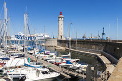 Sete, France. Boats in the port of Sete, Southern France, with the Phare du Mole Saint-Louis lighthouse and the GNV Majestic in the background stock photography