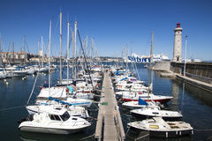 Sete, France. Boats in the port of Sete, Southern France, with the Phare du Mole Saint-Louis lighthouse and the GNV Majestic in the background stock images