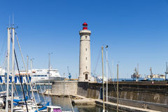 Sete, France. Boats in the port of Sete, Southern France, with the Phare du Mole Saint-Louis lighthouse and the GNV Majestic in the background stock photos