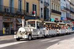 SETE, FRANCE - SEPTEMBER 10, 2017: Excursion locomotive on a city street. Copy space for text. SETE, FRANCE - SEPTEMBER 10, 2017: Excursion locomotive on a city Stock Photos