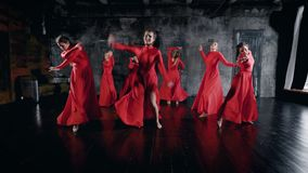 Sete mulheres encantadores dos dançarinos estão dançando em ensaiar o salão, vestidos vermelhos vestindo, encontrando-se no assoa filme