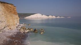 Sete penhascos de giz das irmãs britânicos perto de Eastbourne com dobramento do mar na praia vídeos de arquivo